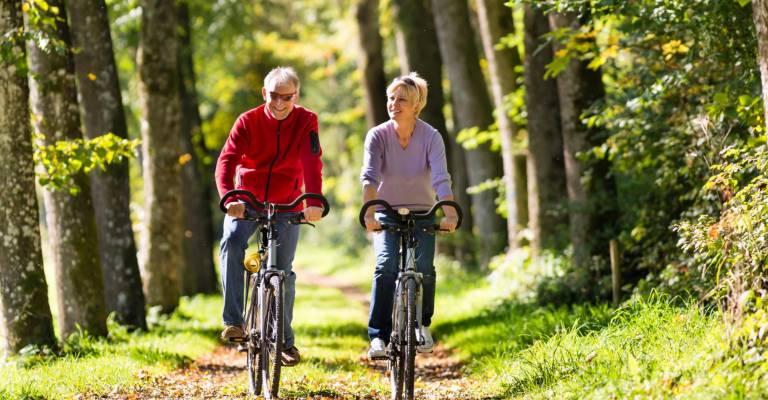 Ouder stel fietst door het bos
