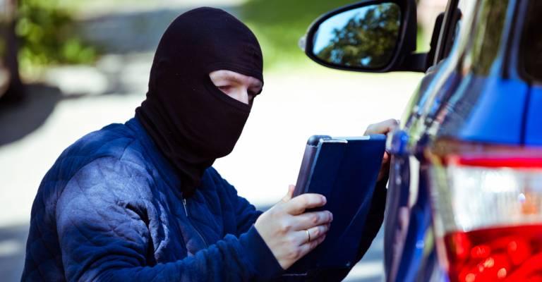 een inbreker bij een auto